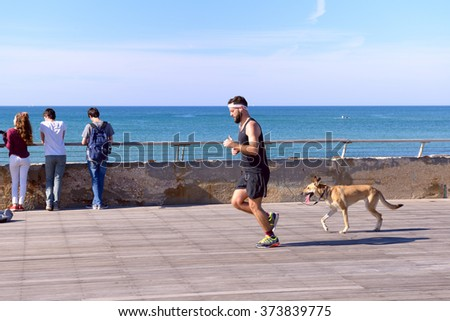 Tel-Aviv, Israel - FEBRUAR 4, 2016: Running man  with the dog on the seafront  in the morning. - stock photo