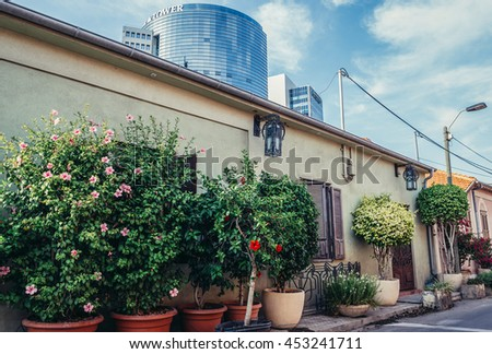 Tel Aviv, Israel - October 20, 2015. Small house with building of Trade Tower on background in historic Neve Tzedek district (lit. Abode of Justice) in southwestern part of Tel Aviv - stock photo