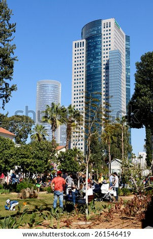 TEL AVIV, ISRAEL- 14.03.2015: People with children are resting in the Sarona park, Tel Aviv. Sarona was a German Templer colony in Tel Aviv, Israel, which is now a neighborhood of the city. - stock photo