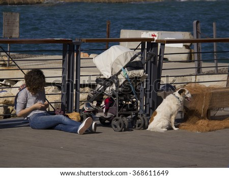 Tel Aviv-Jaffa,Israel .January 15,2015: Woman with smartphone,baby carriage and dog sitting on desk in seaport on sunny day on January 15,2015.Jaffa,Tel Aviv,Israel