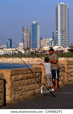 TEL AVIV - OCT 07: Israeli father teaching son to fish  in Tel Aviv, Israel on October 07 2007. Tel Aviv is the most expensive city in the region, and 14th most expensive city in the world.