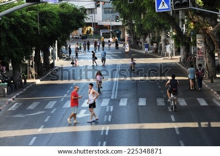 TEL AVIV - October 04, 2014. Day of Atonement (Yom Kippur) in Israel.  Adults and children walk and ride bicycles on the roadway central street, Zina Dizengoff Square - stock photo