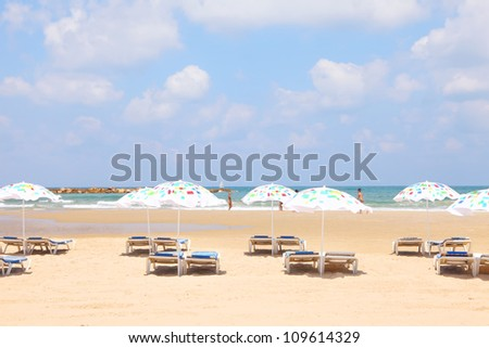 Tel-Aviv sandy beach with colorful umbrellas and lounges (Mediterranean sea. Israel) - stock photo