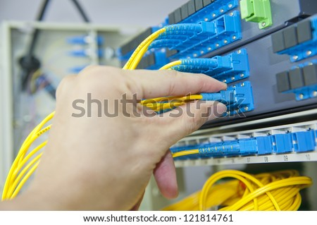 telecom engineer poses on fiber optical network cables patch panel - stock photo