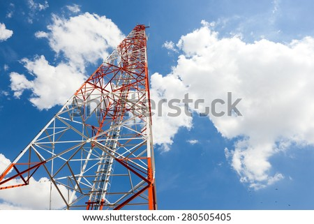 Telecom tower in the afternoon bright sunlight and cloudy blue sky - stock photo