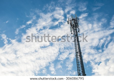 telecommunication antenna on blue and clouds sky.