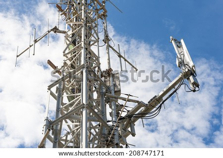 Telecommunication antenna tower against the blue sky - stock photo