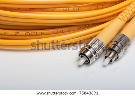Telecommunication background.Twisted fiber optic single mode FC jack over gray background.