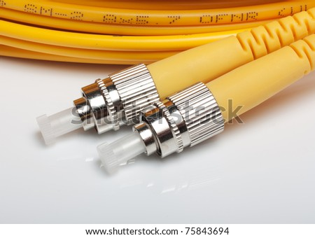Telecommunication background.Twisted fiber optic single mode FC jack over gray background. - stock photo