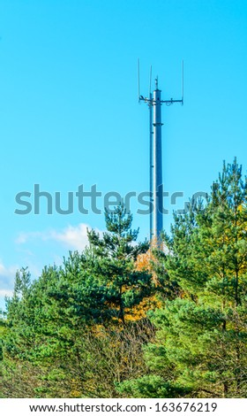 Telecommunication mast and green trees at the blue sky  - stock photo