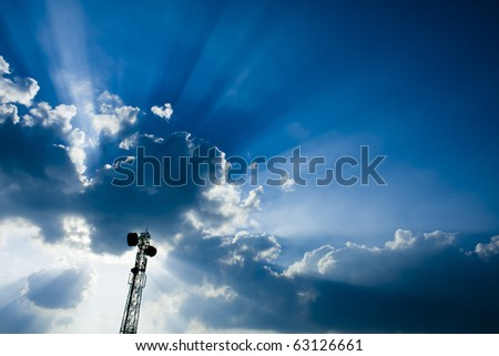 Telecommunication mast / tower with microwave link and TV transmitter antennas over a Beautiful blue sky full with clouds and sun rays. - stock photo