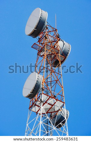 Telecommunication mast with microwave link and TV transmitter antennas on blue sky. - stock photo