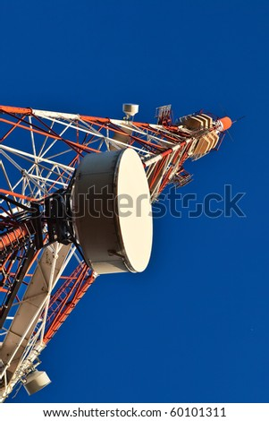 Telecommunication mast with microwave link and TV transmitter antennas over a blue sky. - stock photo