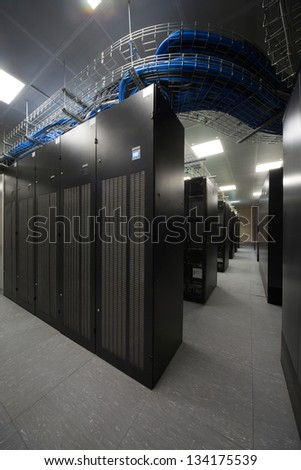 Telecommunication racks in the server room with lots of blue and black cables. - stock photo