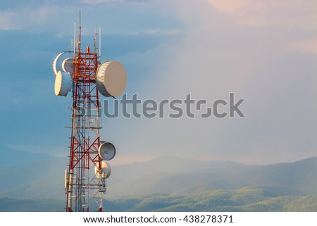 Telecommunication tower at sunset with warm sunlight hitting the tower, blue cloudy sky after the rain, mountain range and distant rain in the background, selective focus on the communication tower - stock photo