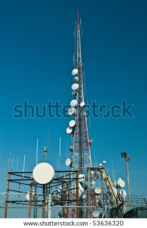 Telecommunication tower behind barbed wire - stock photo