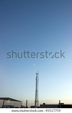 telecommunication tower in an industrial area against evening sky - stock photo