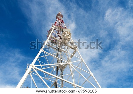 Telecommunication tower with antennas against blue sky background - stock photo