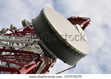 Telecommunication tower with cell phone antenna system against blue sky   - stock photo