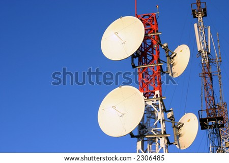 Telecommunication towers on a clear blue sunny day with space for text on the left - stock photo