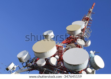 Telecommunications tower against blue sky - stock photo