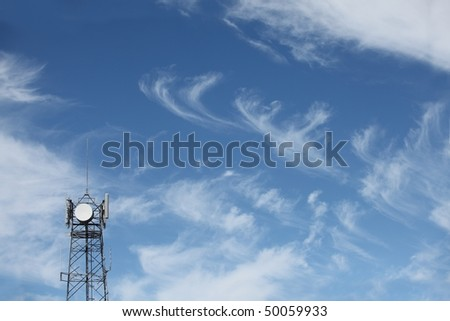 Telecommunications tower against blue sky and cloud backdrop.  Lots of copy space - stock photo