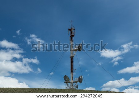 telecommunications tower cellular television toweron blue sky background - stock photo