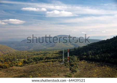 Telecommunications tower in mountains - stock photo