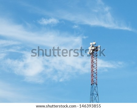 Telecommunications tower on blue cloudy sky background - stock photo
