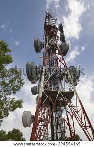 Telecommunications tower with satellite dishes - stock photo