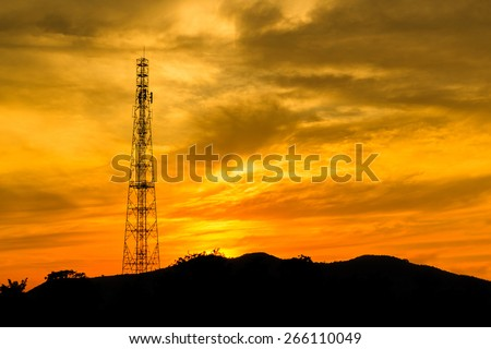 Telecommunications tower with sunset sky, silhouette. - stock photo