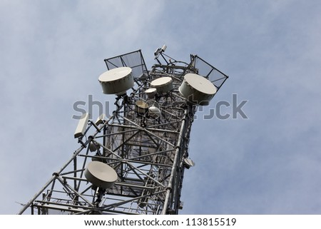 Telecomunication tower with dish and mobile antenas - stock photo