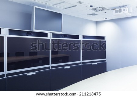 teleconferencing, video conference and telepresence screen display monitor in business meeting room - stock photo