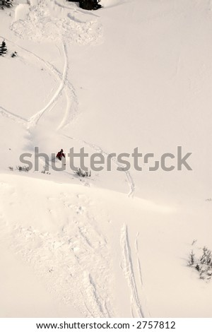 telemark skier in full speed turn out running the avalanche he set off above him - stock photo