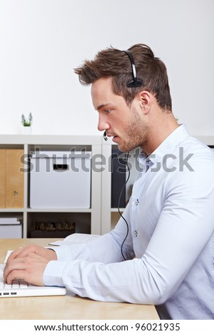 Telemarketing employee with headset working with laptop in office - stock photo