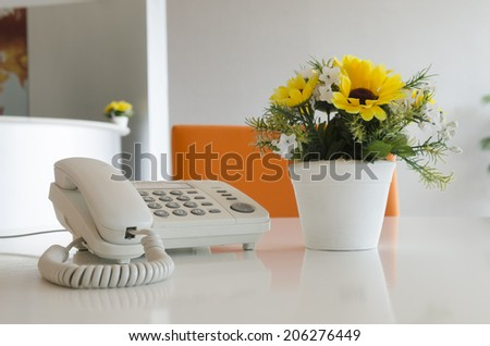 telephone and flower in vase on desk - stock photo