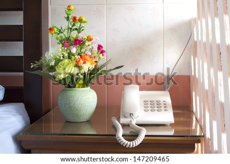 Telephone and flowers on table