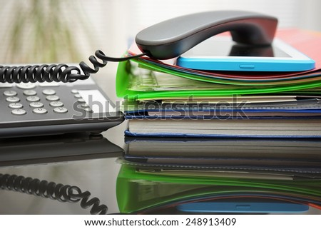 telephone handset and tablet pc on top of the documentation in office - stock photo