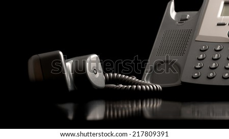 Telephone handset off the hook lying on a black reflective surface alongside the instrument , close up low angle view with copyspace. - stock photo