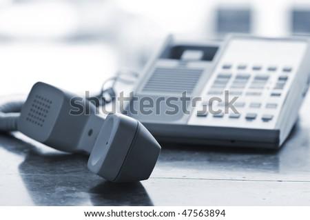 Telephone handset off the hook on desk - stock photo