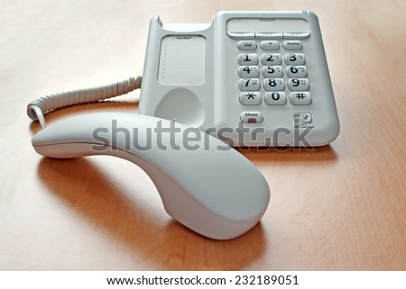 Telephone on an window lit office desk with the receiver off the hook and the call on hold - stock photo