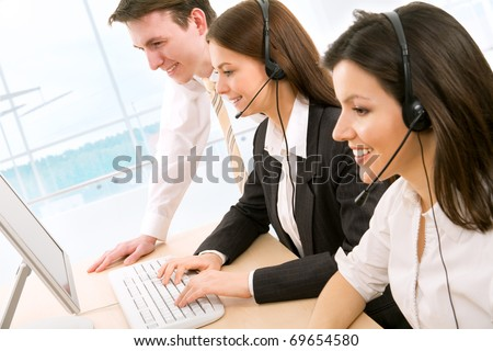 Telephone operators looking at the monitors and working - stock photo