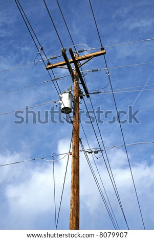 telephone pole with wires against a cloudy blue sky