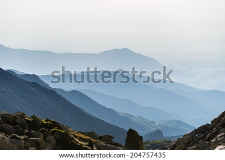 Telephoto view of distant blue toned mountain range arising from the plain below. Location: Piedmont, Italy. - stock photo
