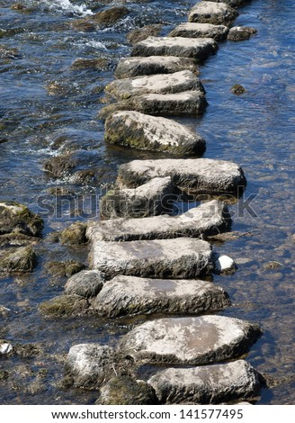 Telephoto view of stepping stones crossing river in Yorkshire Dales. - stock photo