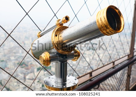 Telescope mounted on top of the Eiffel Tower observation deck. It is wet after rain. View to Paris. - stock photo