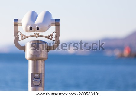 Telescope on a beach pointed at blue sea. - stock photo