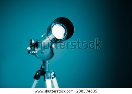 telescope on blue background with copy-space - stock photo