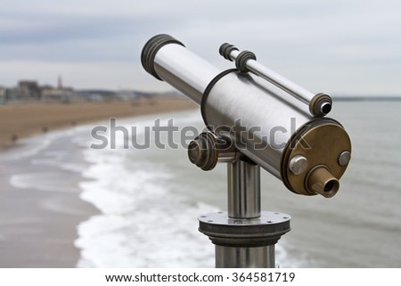 Telescope with the coastline at Scheveningen in the Netherlands in the background - stock photo
