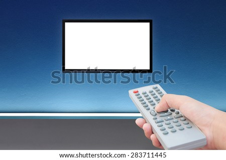 Television and remote control TV on blue wall and light  - stock photo